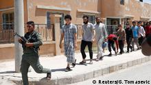 24.06.2017+++ Raqqa, Syrien Islamic State prisoners, who were pardoned by a council that is expected to govern Raqqa once the group is dislodged from the Syrian city, walk behind a Kurdish policeman in Ain Issa village, north of Raqqa, Syria June 24, 2017. REUTERS/Goran Tomasevic