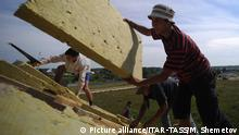 Construction workers put thermal insulation into the roof of a new house (Picture alliance/ITAR-TASS/M. Shemetov)