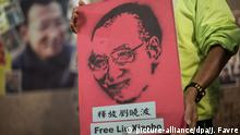 epa05082199 An activist with the Hong Kong Alliance in Support of Patriotic Democratic Movements of China celebrates the 60th birthday of imprisoned human rights activist and 2010 Nobel Peace Prize laureate Liu Xiaobo in Hong Kong, China, 28 December 2015. Liu is currently incarcerated as a political prisoner in China for calling for political reforms and the end of communist single-party rule. EPA/JEROME FAVRE |