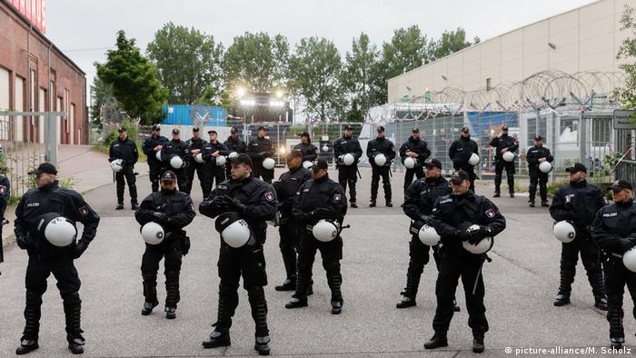Полицейские у входа во временный пункт приема задержанных правонарушителей под Гамбургом