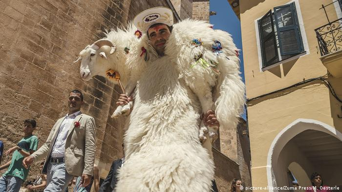 Man with sheep draped over his shoulders (picture-alliance/Zuma Press/M. Oesterle)