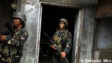 25.06.2017***Philippines army soldiers stand in a house as government forces continue their assault against insurgents from the Maute group, who have taken over large parts of Marawi City, Philippines June 25, 2017. REUTERS/Jorge Silva