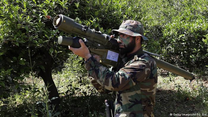 A Hezbollah fighter stands with a rocket launcher in a grove of trees