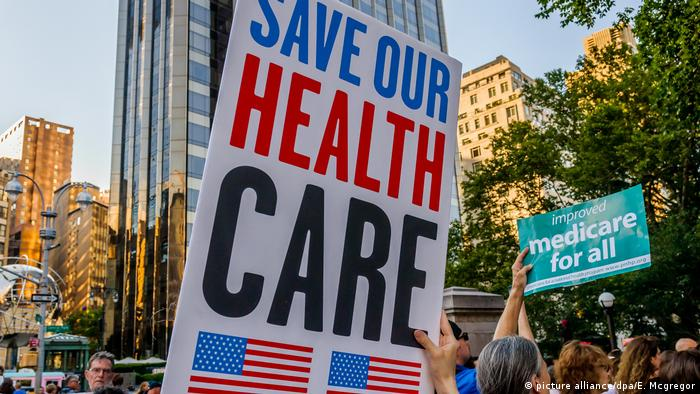 A protester holds up a placard with the words 'Save our health care' during a June 2017 protest against changes to Obamacare pursued by the Trump administration (picture alliance/dpa/E. Mcgregor)