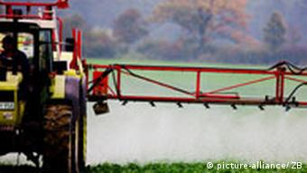 Farmer spraying pesticides over field with tractor fitted with spraying arms.