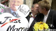 FILE PHOTO: Munich gay couple Dietmar Holzapfel (R) and Josef Scattler kiss as they protest at the Marienplatz in Munich, Germany, against the Bavarian state government for an officially registered partnership August 1, 2001. German law allows gays and lesbians in most German states from today on to officially register their partnerships and enjoy many of the same tax and pension benefits as heterosexual couples. The picture on the left shows Bavarian State Prime Minister Edmund Stoiber saying No. REUTERS/Tobias Schwarz/File Photo