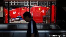 27.06.2017*****A man walks past Chinese and Hong Kong flags ahead of 20th anniversary of the handover from Britain to China, in Hong Kong, China June 27, 2017. REUTERS/Tyrone Siu