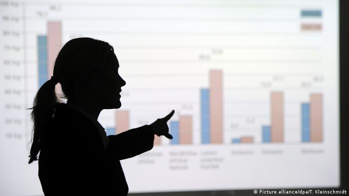 Silhouette of a woman pointing to a graph