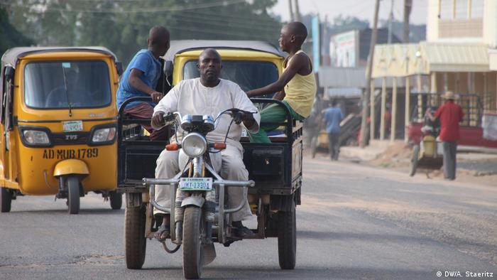 A man rides a tuk tuk on the border road between Nigeria and Cameroon in Mubi. (DW/A. Staeritz)