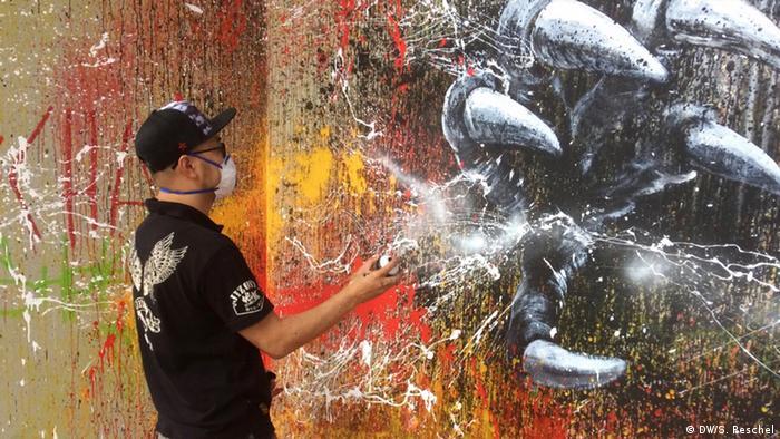 Chinese street artist Qi Xinghua painting in Gleisdreieck, a famous park in Berlin