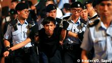 A pro-democracy activist is carried by policemen as protesters are arrested at a monument symbolising the city's handover from British to Chinese rule