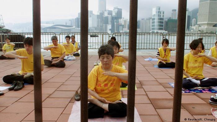 Pessoas em camisetas amarelas sentadas no chão fazem meditação