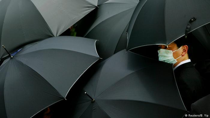 Vários guarda-chuvas pretos e uma pessoa com máscara cirúrgica