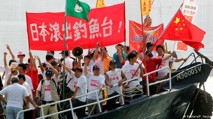 Pessoas em barco empunham faixas de protesto