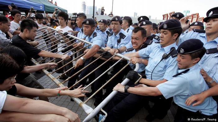 Policiais e manifestantes puxam uma cerca,cada um de um lado