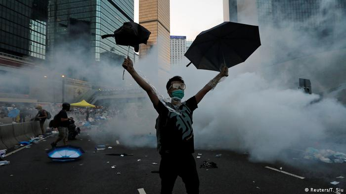 Homem com óculos de segurança e máscara cirúrgica à frente de uma nuvem de fumaça