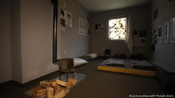 Sala despojada com fogão e lenha no chão