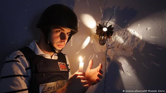 Homem com capacete segura vela acesa