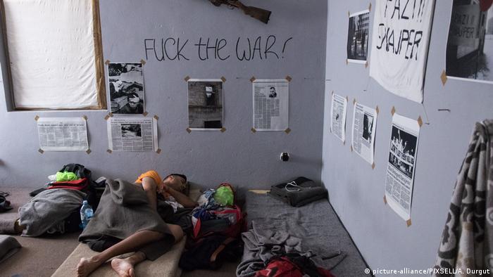 Ein Mann liegt auf einer Matratze am Boden, Zeitungsartikel an den Wänden (Foto: Picture Alliance)