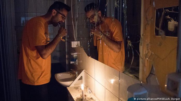 Ein Mann putzt sich bei Kerzenschein die Zähne vor einem zersplitterten Spiegel (Foto: Picture Alliance)