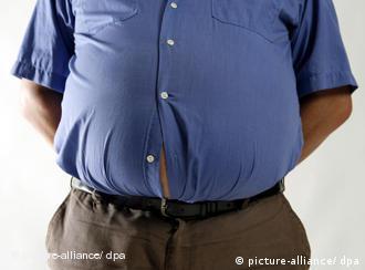 Ein übergewichtiger Mann, bei dem sich ein Knopf am Hemd geöffnet hat
