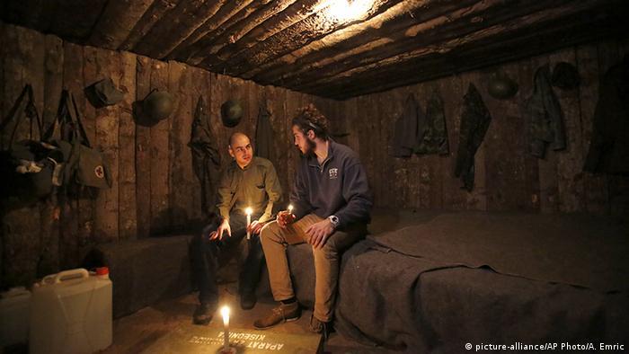 Zwei Männer sitzen bei Kerzenschein in einem mit Holzstämmen verkleideten Raum (Foto: Picture Alliance)
