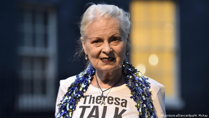 Vivienne Westwood wears a blue scarf made of sequins over a while t-shirt