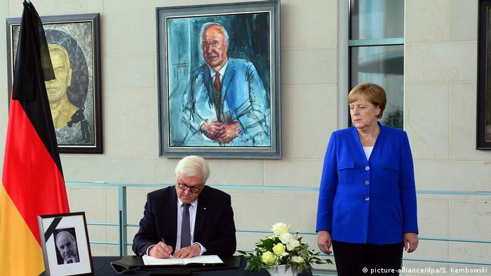 Angela Merkel stands next to Frank-Walter Steinmeier as he signed a condolence book after the death of Helmut Kohl