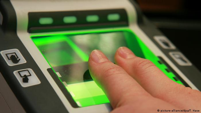 A person holds both thumps against an electronic fingerprint scanner (picture-alliance/dpa/T. Hase)
