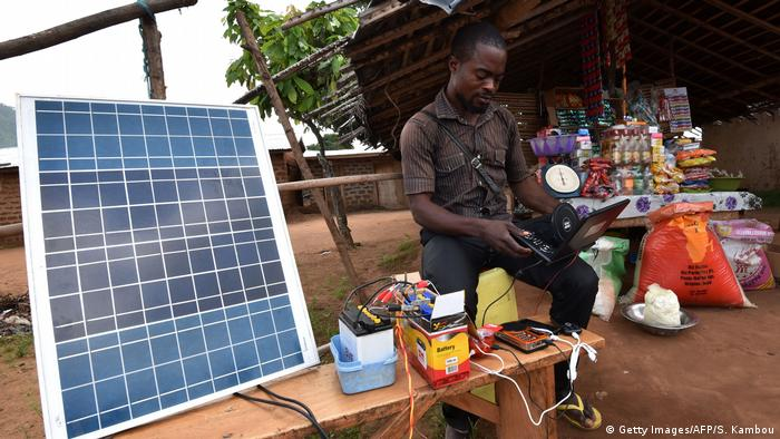 DW eco@africa - A man uses a laptop connected to a solar panel (Getty Images/AFP/S. Kambou)