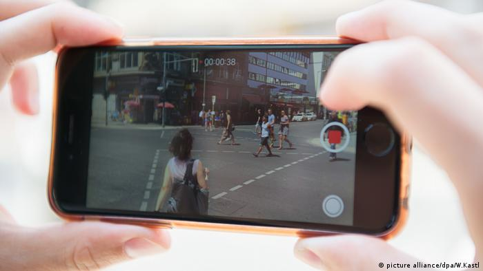 Person films video on smartphone (picture alliance/dpa/W.Kastl)
