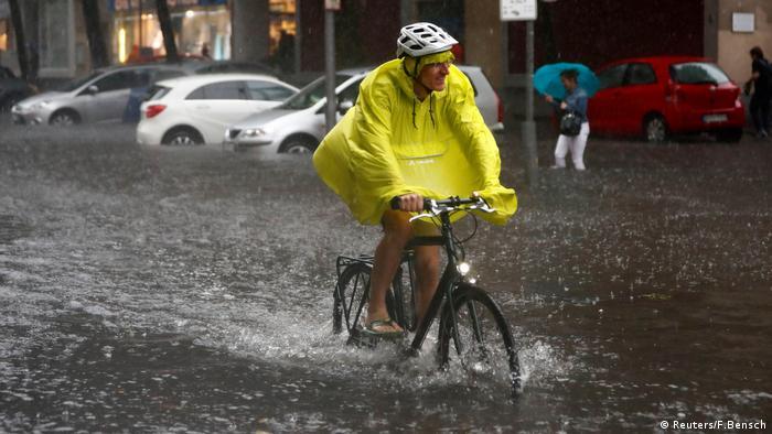 Ciclista pedala em rua inundada em Berlim