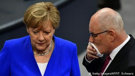 Heads bowed, Kauder (R), with a white hankerchief over his mouth consults with Merkel in the Bundestag chamber (Getty Images/AFP/T. Schwarz)