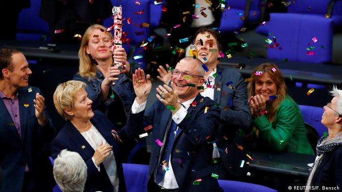Greens parliamentarian Volker Beck, standing, being showered with confetti by colleagues in parliament (REUTERS/F. Bensch)