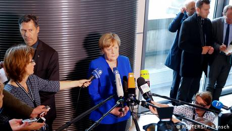 Merkel surrounded by microphones and journalists in parliament's canteen (REUTERS/F. Bensch)