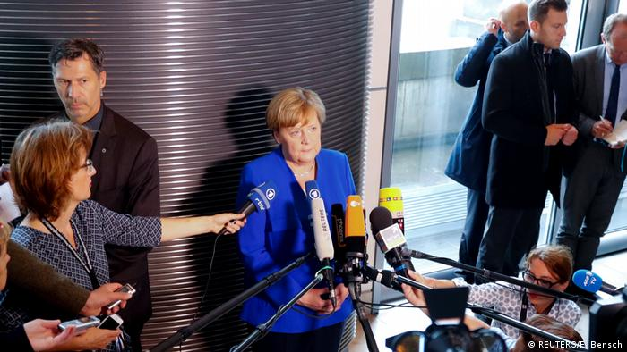 Merkel surrounded by microphones and journalists in parliament's canteen