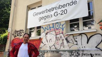 Вальтер Винкельман в Гамбурге перед своей мастерской с транспарантом Ремесленники против G20.