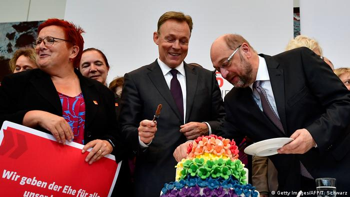 Leading Social Democrats Martin Schulz and Thomas Oppermann slice into a multicolored, multilayered cake after Friday's vote (Getty Images/AFP/T. Schwarz)