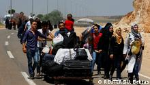 REFILE - Syrians, who say they are returning to Syria ahead of the Eid al-Fitr, carry their belongings as they walk to the Turkish Cilvegozu border gate, located opposite of Syrian crossing point Bab al-Hawa in Reyhanli, in Hatay province, Turkey, June 15, 2017. REUTERS/Umit Bektas