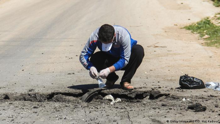 a man is bending over rubble on the road, collecting samples.