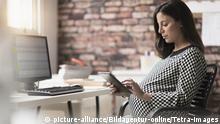 Pregnant woman working in office, Schwangere Frau, die im Büro arbeitet