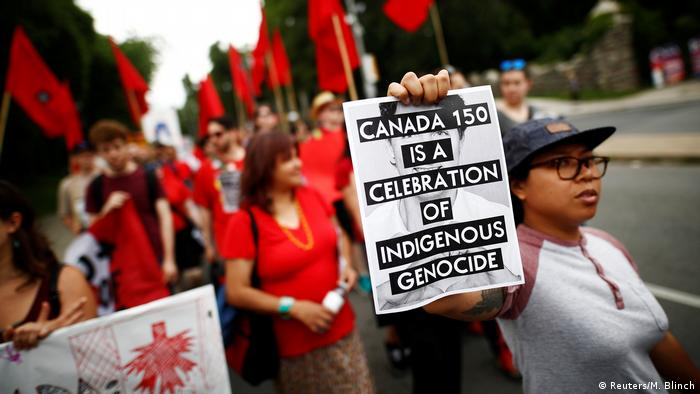 An indigenous rights activist holds a sign reading Canada 150 is a Celebration of Indigenous Genocide (Reuters/M. Blinch)