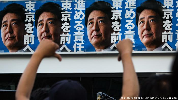 Japanese Prime Minister Shinzo Abe's campaign posters is seen from atop of a campaign van with anti-Abe protestor during election campaign for Tokyo Metropolitan Assembly (picture-alliance/NurPhoto/R. A. de Guzman)