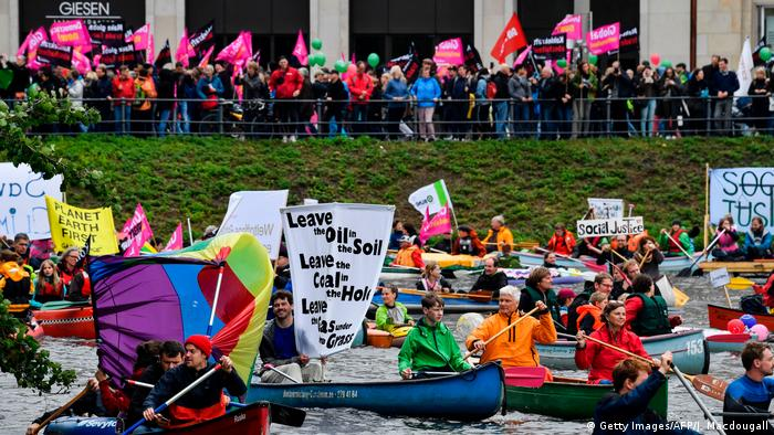 Protest boats pass demonstrators on the Alster river during a demonstration called by several NGOs ahead of the G20 summit in Hamburg
