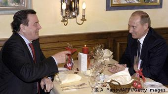 Schroeder and Putin share a laugh over dinner in 2004.