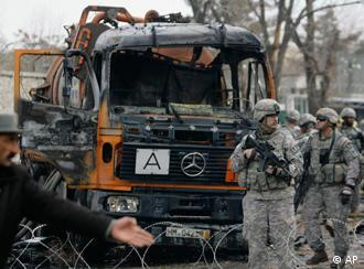 A US soldier, left, talks on a radio after a suicide attack in Kabul, Afghanistan, on Saturday, Jan. 17, 2009.