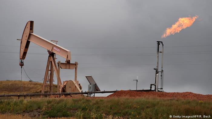 Pump jacks and a gas flare are seen near Williston, North Dakota, on September 6, 2016