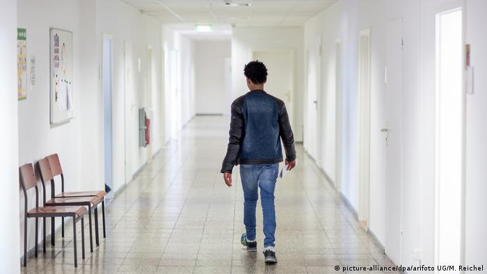 A refugee walks in a hallway at a reception center in Suhl, Germany