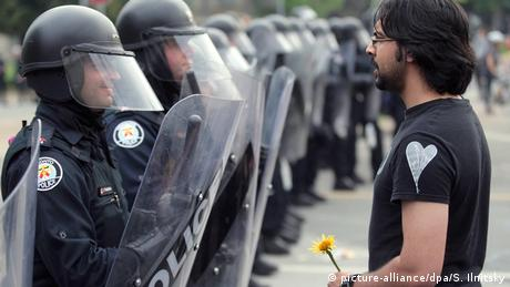 A protester stands in front of police officers during a march against the G20 and the G8 summits in Toronto, Ontario, Canada on 26 June 2010 (picture-alliance/dpa/S. Ilnitsky)