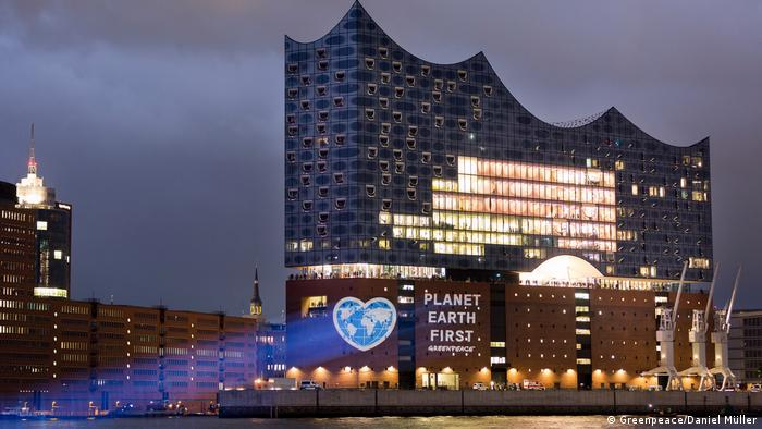 Greenpeace activists project an image of the earth, shaped like a heart, onto the Elbe Philharmonic Hall in Hamburg